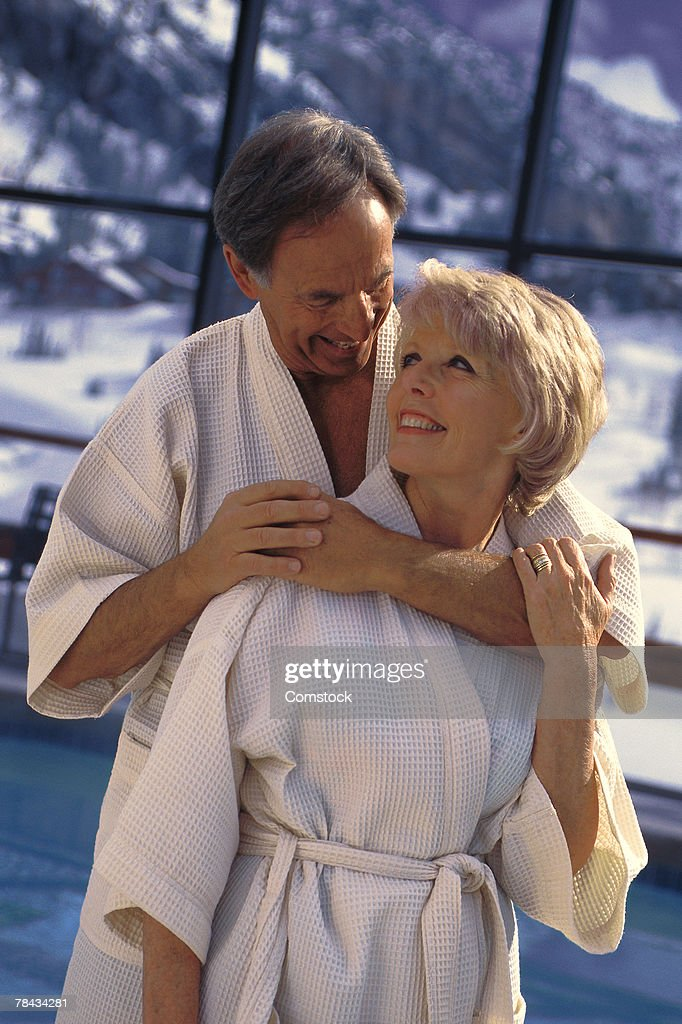 Couple hugging near indoor pool at resort : Stock Photo