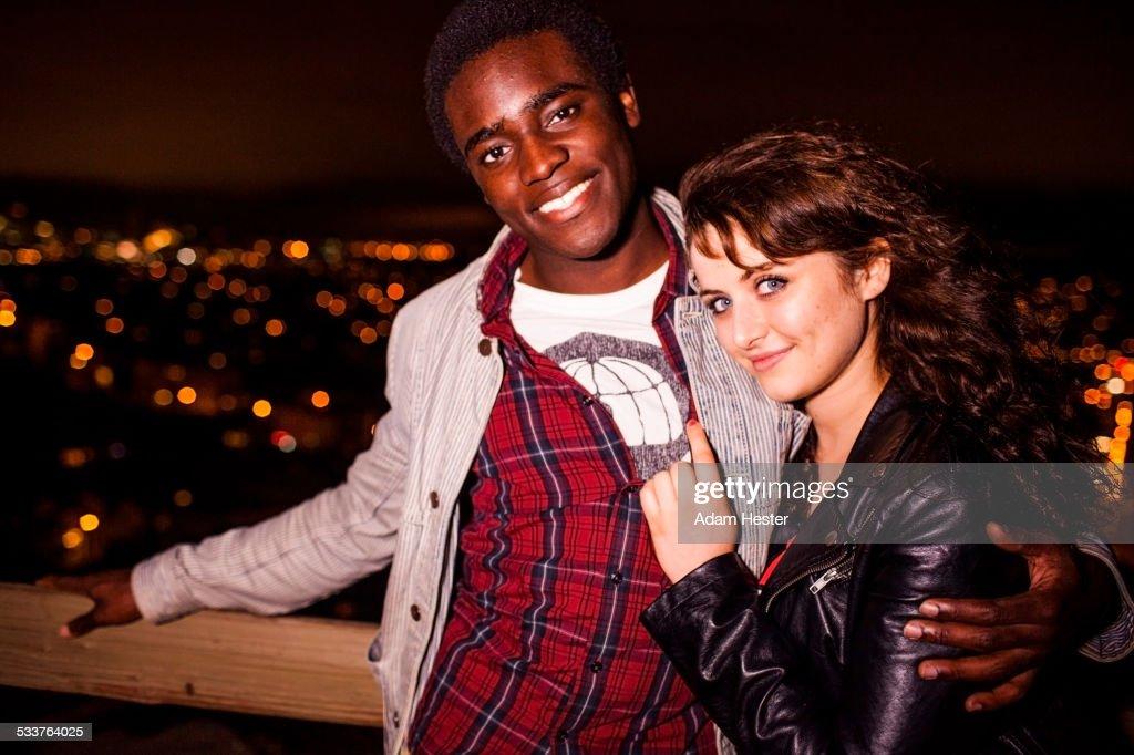 Couple hugging near scenic view of cityscape at night : Foto stock