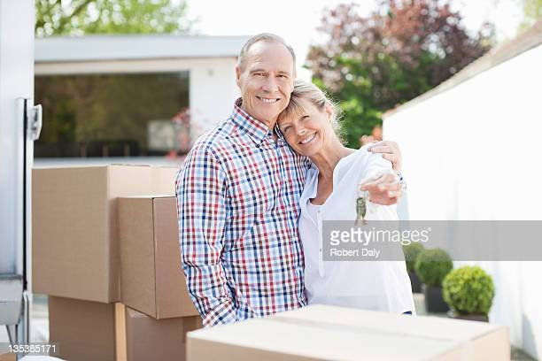 Couple hugging near stack of moving boxes