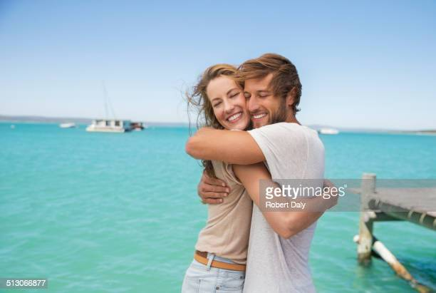 Couple hugging near water