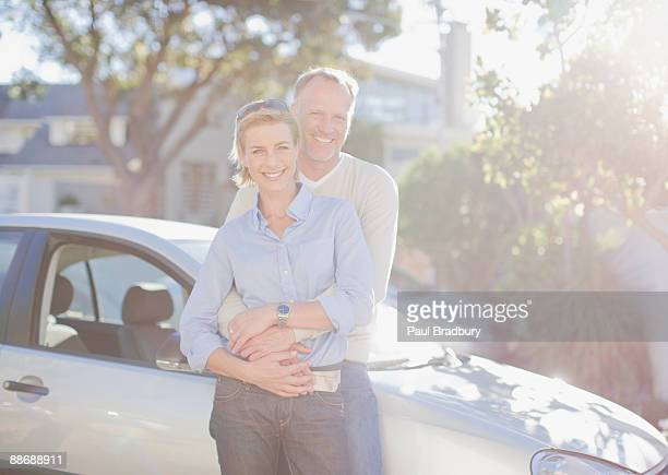 Couple hugging next to car