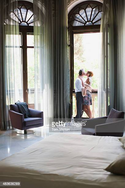 Pareja abrazándose en el balcón de la habitación
