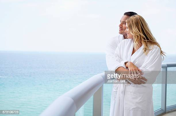 Couple hugging on balcony over ocean