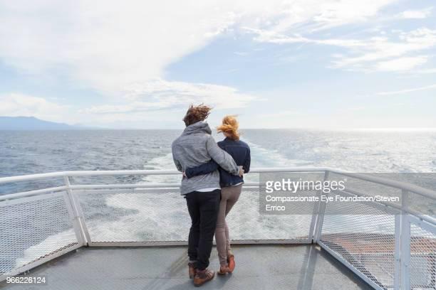 couple hugging on boat deck looking at ocean view - geländer stock-fotos und bilder