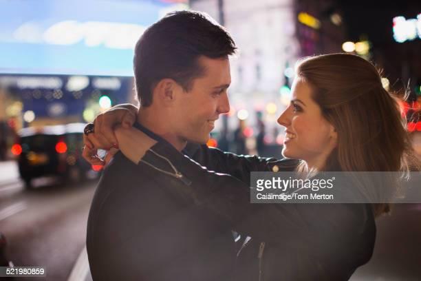 Couple hugging on city street at night