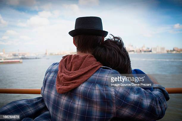 Couple hugging on ferry in urban harbor