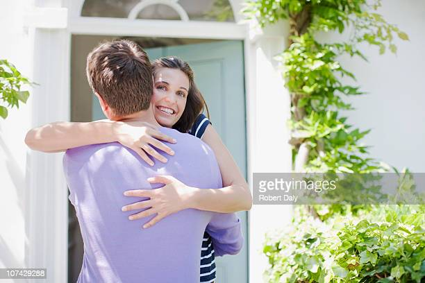 Couple hugging on front stoop