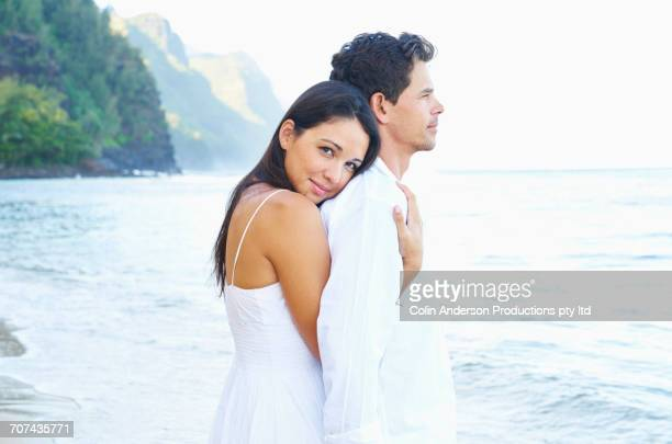 couple hugging on sunny ocean beach - heterosexual couple stock pictures, royalty-free photos & images