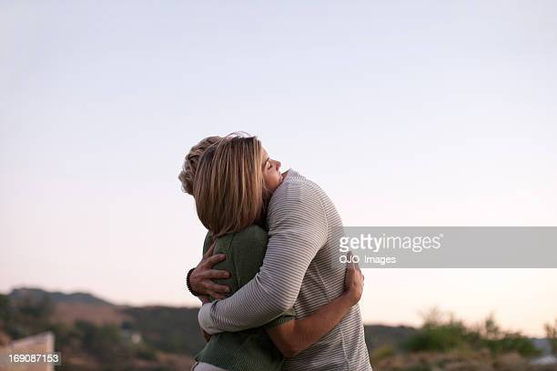 couple hugging outdoors - echtgenote stockfoto's en -beelden