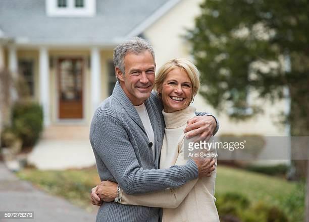 Couple hugging outside house