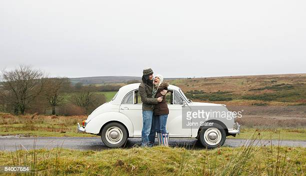 couple hugging outside old car - clear sky stock pictures, royalty-free photos & images