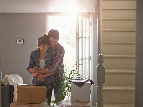 A couple hugging playfully in their new home - gettyimageskorea