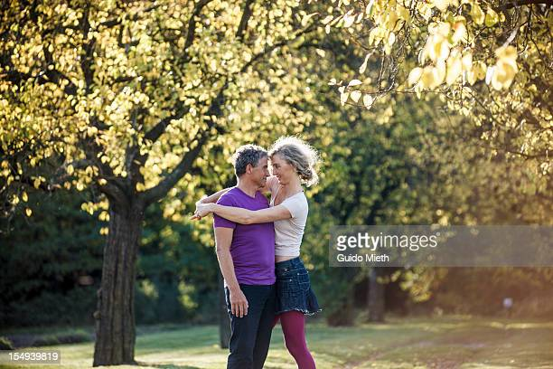 Couple hugging under big tree in park.