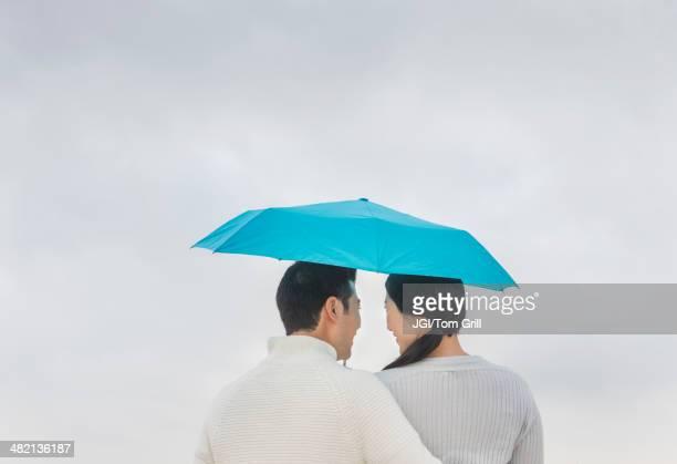 Couple hugging under umbrella