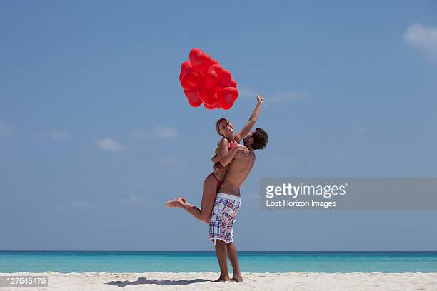 Couple hugging with balloons on beach