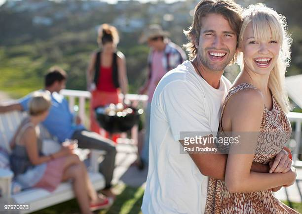 Couple hugging with friends at barbecue