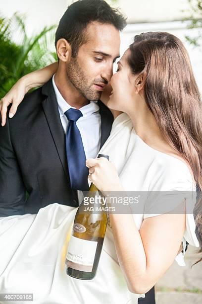 Couple hugging, woman holding wine bottle