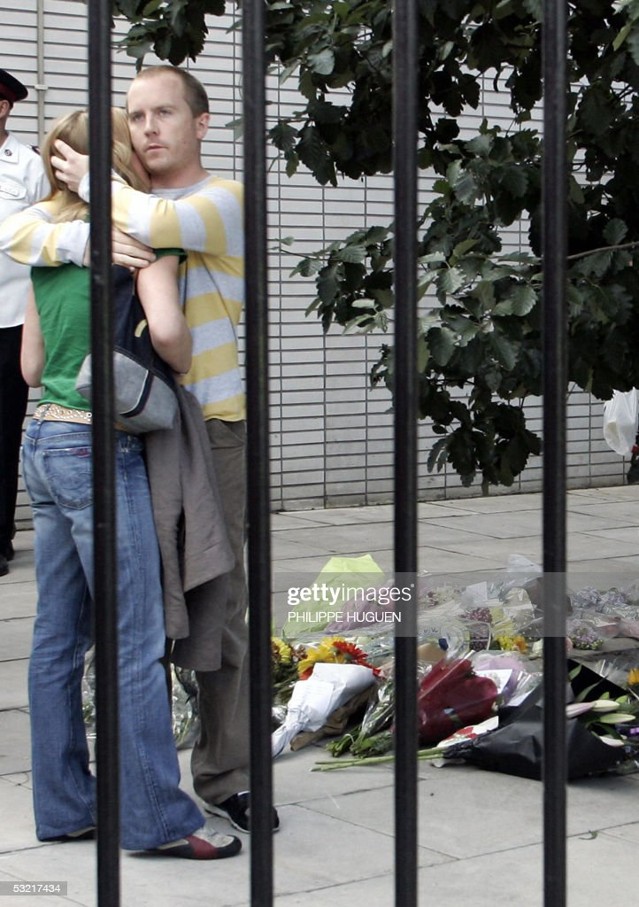 A couple hugs near flowers left in memory of the victimes of the bomb attacks at King's Cross in London 09 July 2005. In London's hushed streets, rapidly-expanding floral shrines and anguished posters appealing for scraps of information about missing loved ones were a constant reminder of the bombing attacks.