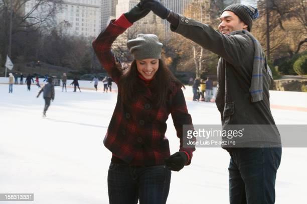 couple ice skating and holding hands - eislaufbahn stock-fotos und bilder