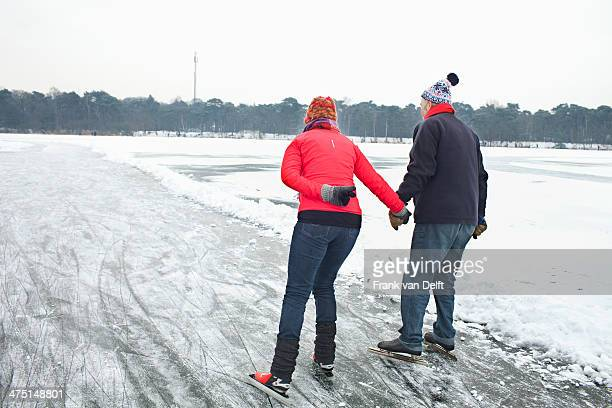 Couple ice skating, holding hands