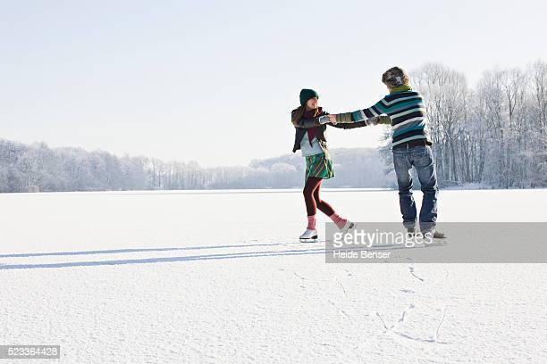 Couple Ice Skating on Frozen Pond