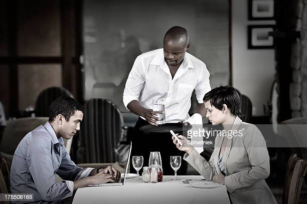 Couple ignoring each other at dinner