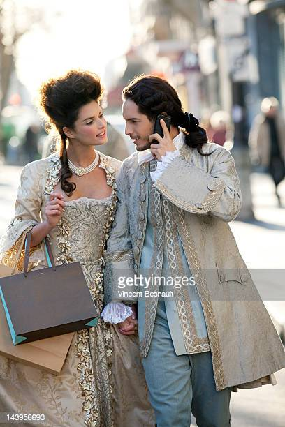 A couple in 18th century garb go shopping