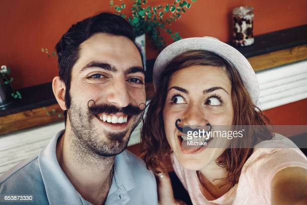 Couple in a bar gesturing for selfie