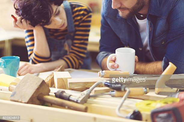 Couple in a construction workshop, learning carpentry