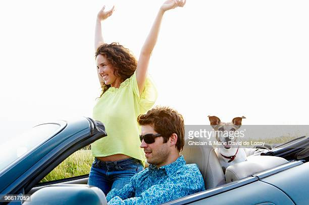 Couple in a convertible, with dog