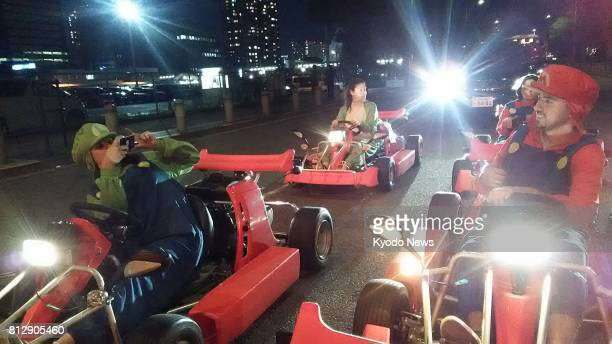 A couple in a group of four Australians takes photos at an intersection during a twohour gokarts tour in central Tokyo on June 17 2017 ==Kyodo