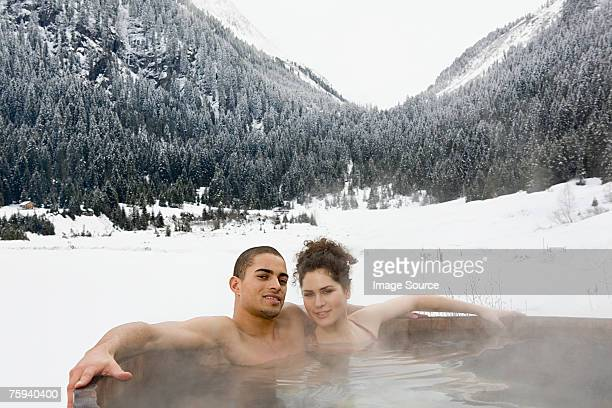 Couple in a hot tub near mountains