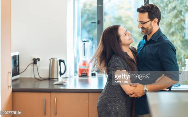 Couple in a light moment in kitchen.