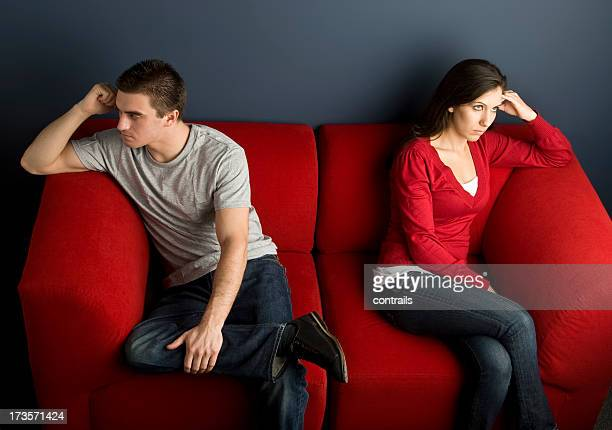 A couple in a little disagreement sitting on red couch