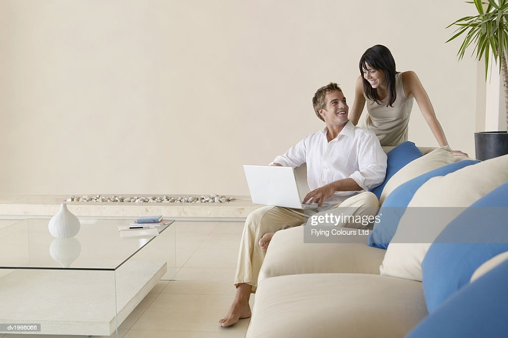 Couple in a Modern Living Room, Man Using a Laptop Computer : Stock Photo