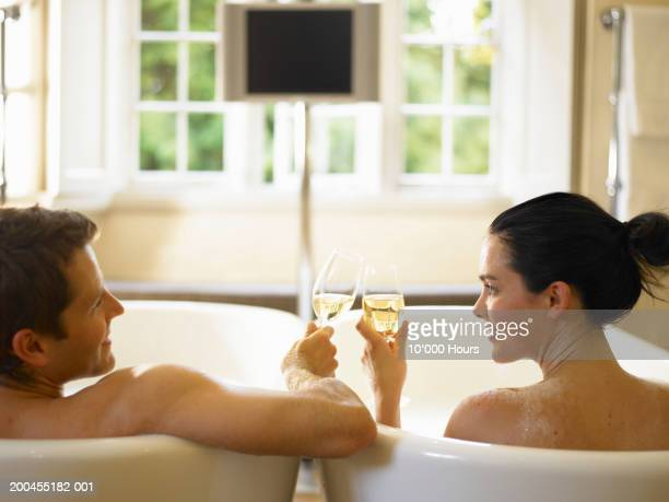 couple in adjacent bubble baths, toasting champagne glasses, rear view - couple bathtub stock pictures, royalty-free photos & images