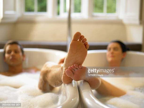 Couple in adjacent bubble baths, touching feet