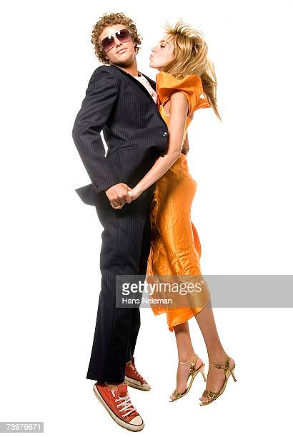 Couple in alternative evening wear jumping in the air