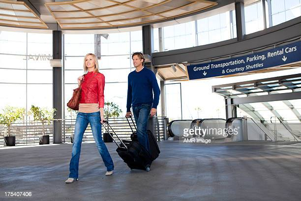 Couple in an airport with suitcases.