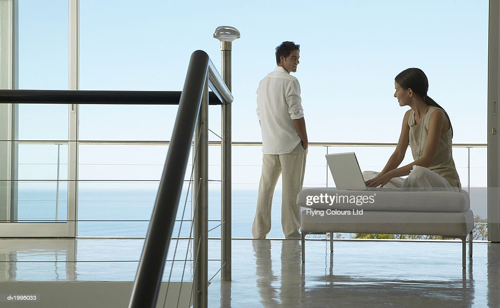 Couple in an Apartment, Woman Using a Laptop and a Man Standing With His Hands in His Pockets : Stock Photo