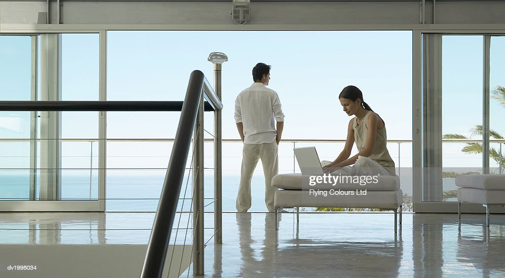 Couple in an Apartment, Woman Using a Laptop and a Man Standing With His Hands in His Pockets Looking at the View : Stock Photo