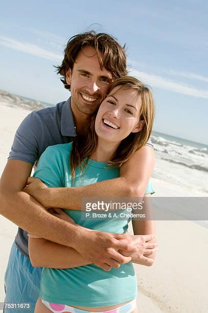 Couple in an embrace, on the beach, posing for the camera, outdoors