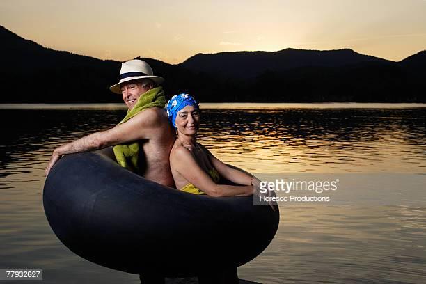 Couple in an innertube by a lake