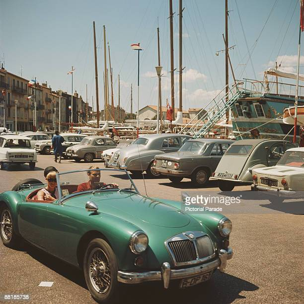 Couple in an MG sports car at the harbour in St Tropez, France, circa 1965.