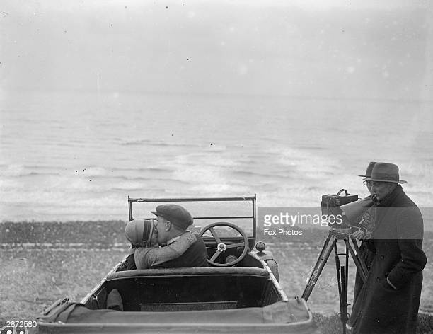 A couple in an open car locked in a passionate embrace for a scene in the film The Thrill being shot on Brighton beach