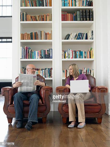 Couple in Armchairs with Newspaper and Laptop