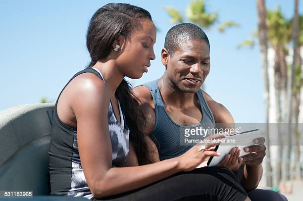 Couple in Athletic Work Out Clothing Reviewing Computer Tablet