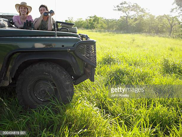 Couple in back of jeep holding binoculars