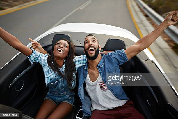 Couple in backseat of car with arms in the air
