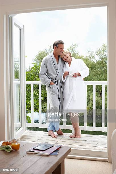 couple in bathrobes drinking coffee on balcony - bathrobe stock pictures, royalty-free photos & images